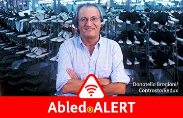 Abled.ALERT: Photo of famed Italian shoe designer Sergio Rossi standing with his arms crossed and smiling in front of an automated rack of shoe forms at a factory in Italy.
