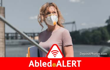 Abled.ALERT: Stock photo of a woman carrying file folders wearing a protective face mask while crossing a fiver on a footbridge.