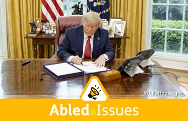 Abled.Issues: Photo of U.S. President Donald Trump signing a document at his desk in the Oval Office of the White House.