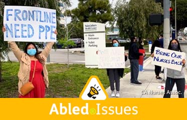 """Abled.Issues: Photo shows Nurses protest working conditions outside St. John's Medical Center in Santa Monica, California on Friday, April 17, 2020. One nurse holds up a large sign reading """"Frontline Need PPE"""", while another holds a smaller sign reading """"Bring our nurses back""""."""