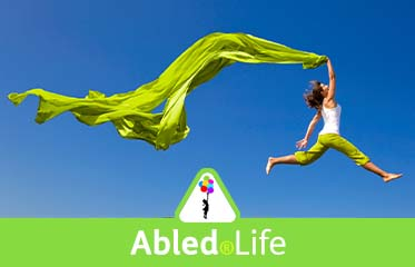 Abled.Life: Photo of a woman leaping above the ground while trailing a long green fabric that matches the color of her slacks and the Abled logo.