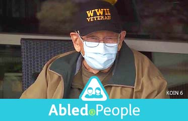 Abled.People: Photo of 104 year-old Bill Lapschies wearing a surgical mask and wearing a WW II Veteran cap while sitting in a wheelchair outside a Veteran's home in Lebanon, Oregon.