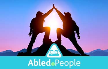Abled.People: Photo of two people giving each other a high five at the top of a mountain summit with the sun in the background.