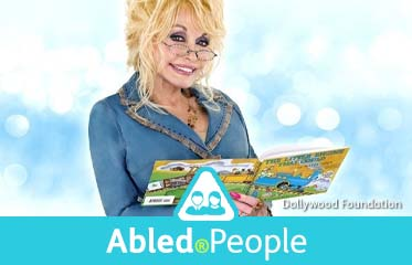 "Abled.People: Photo of music icon Dolly Parton wearing reading glasses and holding the book ""The Little Engine That Could""."