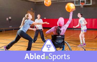 Abled.Sports: Photo of a group of teens, including one in a wheelchair, playing volleyball in a circle.
