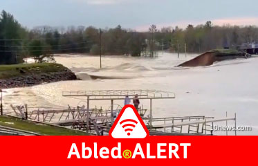 Abled.ALERT: Video frame shows flooding and a raised road breached after a dam failure in Edenville, Michigan.