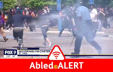 Abled.ALERT: Emergency: Safety Alert. Image: Video still frame of a police officer spraying tear gas at protestors in Minneapolis on a sunny afternoon.