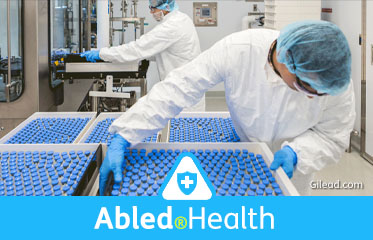 Abled.Health: Corporate photo of lab workers in protective gear willing and moving trays containing vials of medicine at Gilead Sciences.