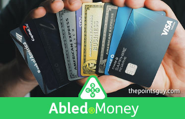 Abled.Money: Photo of a man's hands holding a Buch of credit cards like spread out playing cards.