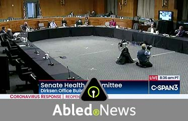 Abled.News: Video still of a wide shot inside the Dirksen Office Building of a u-shaped layout of tables for a Senate Health Committee teleconference hearing.