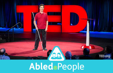 Abled.People: Photo of Daniel Kish speaking at the global TED Conference. He is standing on a round carpet on stage with the red TED logo lit-up behind him. He is holding a full-length Perception Cane.
