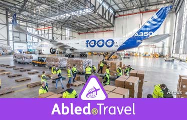 Abled.Travel: Photo of Airbus employees preparing to load boxes of PPE (Personal Protective Equipment) onto a Beluga Super Transporter plane in a hangar.