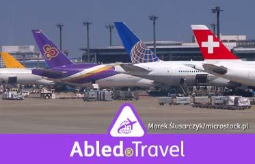 Abled.Travel: Photo of the tail sections of aircraft parked at their respective gates at Tokyo's Narita Airport, showing the logos of Swiss International Air Lines, United Airlines, and Thai Airways International.