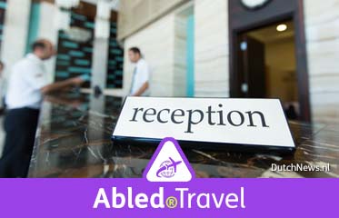 "Abled.Travel: Photo shows a ""Reception"" sign floating in the foreground with a blurred image of a customer checking in at a hotel front desk in the background."