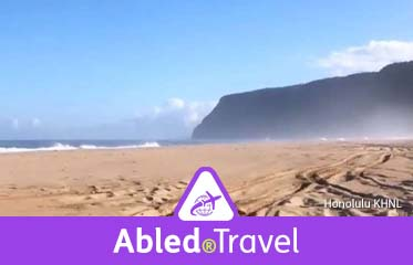 Abled.Travel: Photo of a beach on the Hawaiian island of Kauai with cliffs in the background.