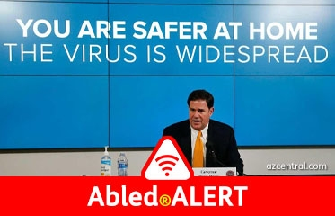 "Abled.ALERT:Arizona Governor Doug Ducey gives a press conference as words on digital screens behind him read ""You are safer at home. The Virus is widespread."""