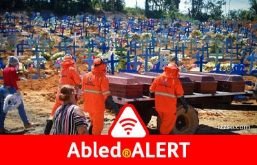 Abled.ALERT: Workers in orange protective gear wheel a trailer loaded with six coffins through a graveyard in Brazil marked by a hillside of blue crosses.