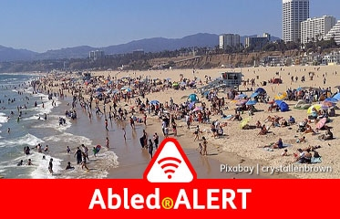 Abled.ALERT: Photo of people on Santa Monica Beach in Los Angeles looking north towards the mountains.