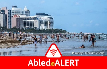 Abled.ALERT: Photo of many people on South Beach in Miami, Florida with beachfront hotels and condos in the background.