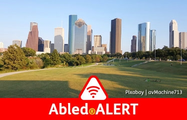Abled.ALERT: Photo of skyline of downtown Houston from across a park.