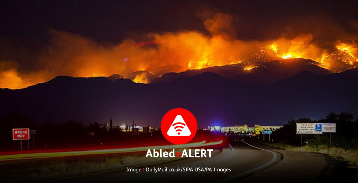 Abled.ALERT: Night time photo showing flames shooting into the air in the mountain-top Tonto National Forest northeast of Phoenix, Arizona.