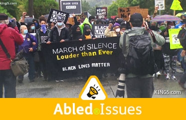 """Abled.Issues: Video frame of protestors taking part in Seattle's March of Silence on a rainy day. People at the front carry a banner that reads """"March of Silence. Louder than ever. Black lives matter."""""""