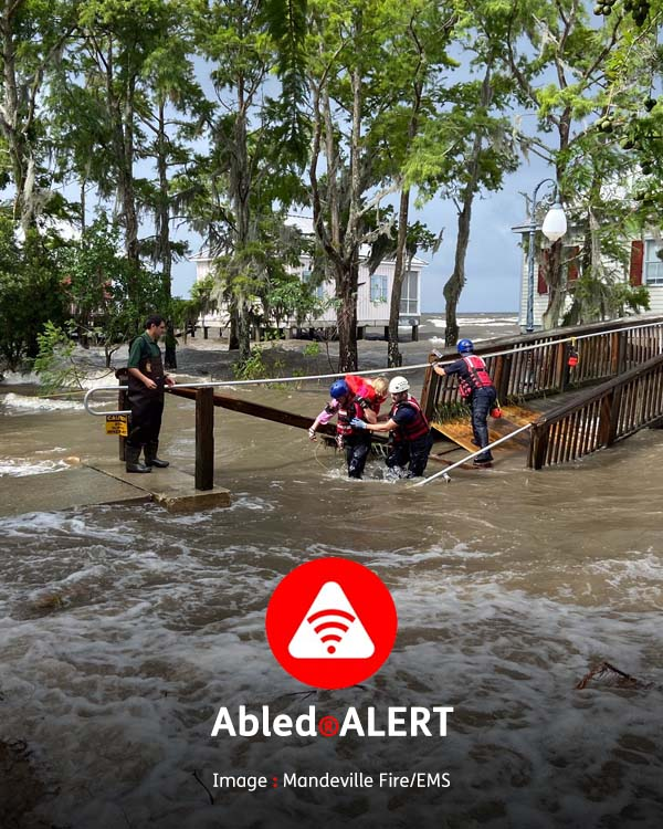 Abled.ALERT: Weather: Members of the Mandeville Fire/EMT water rescue team carry occupants from lakefront cabins cut-off by storm surge flooding at Fontainebleu State Park in Louisiana.