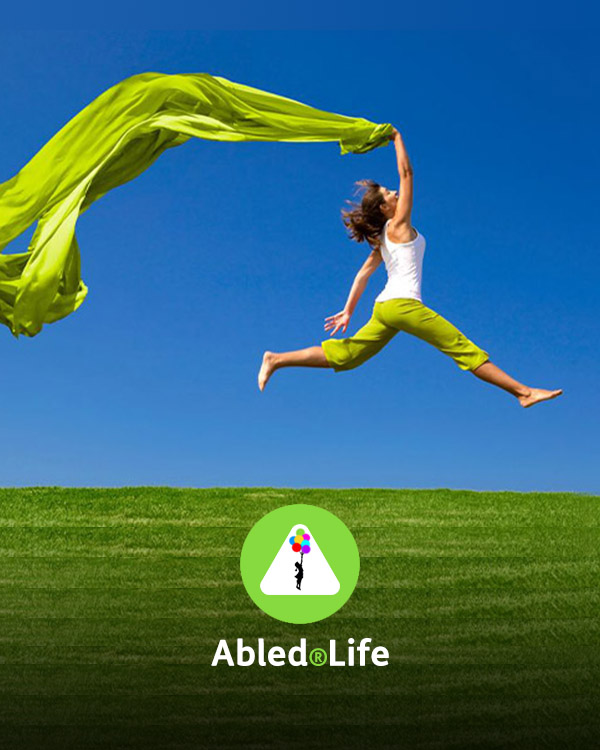Abled.Life Directory Link: Photo of a woman in a white top and green pants leaping above a grassy hill while holding a green banner.