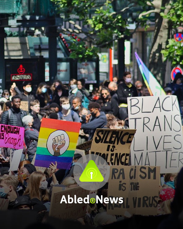 "Abled.News Directory link. Photo of a mass protest on a downtown city street with people holding signs reading ""Enough is enough"", ""Silence is Violence"", ""Racism is the real virus"" and ""Black trans lives matter""."
