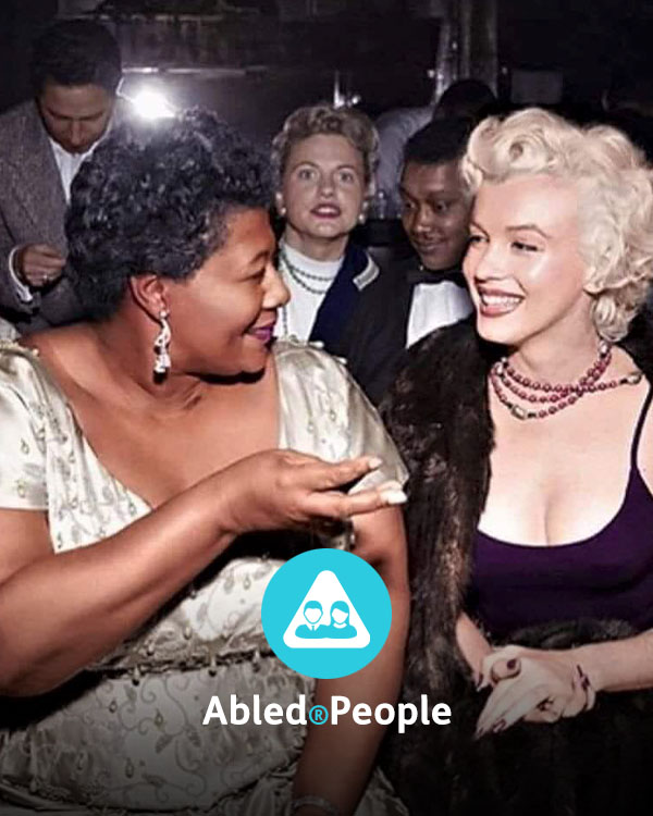 Abled.People Directory link. Photo of Jazz icon Ella Fitzgerald sitting next to screen icon Marilyn Monroe as they chat at the Mocambo nightclub in Hollywood.
