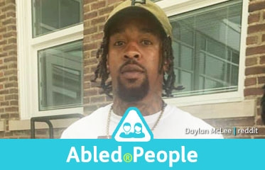 Abled.People: Photo of Daylan McLee wearing a white t-shirt with a baseball cap.