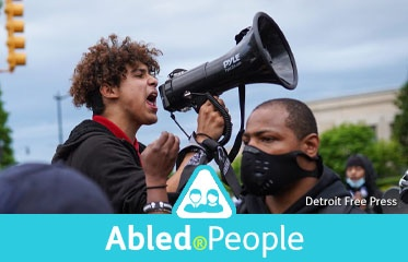 Abled.People: Photo of 16 year-old Stefan Perez u speaking through a megaphone and urging protestors in Detroit to respect a curfew.