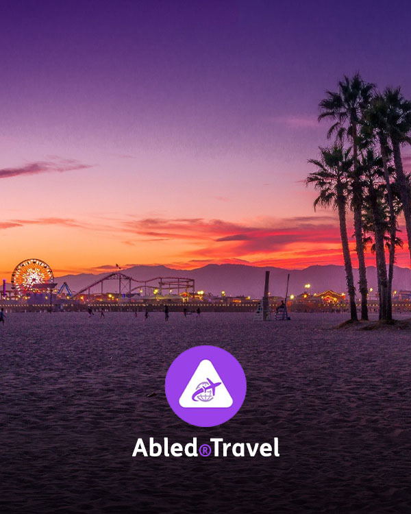 Abled.Travel Directory link. Photo of Santa Monica Beach at dusk with the Santa Monic Pier all lit up and silhouetted palm trees set against the orange and purple sky above the mountains in the distance.