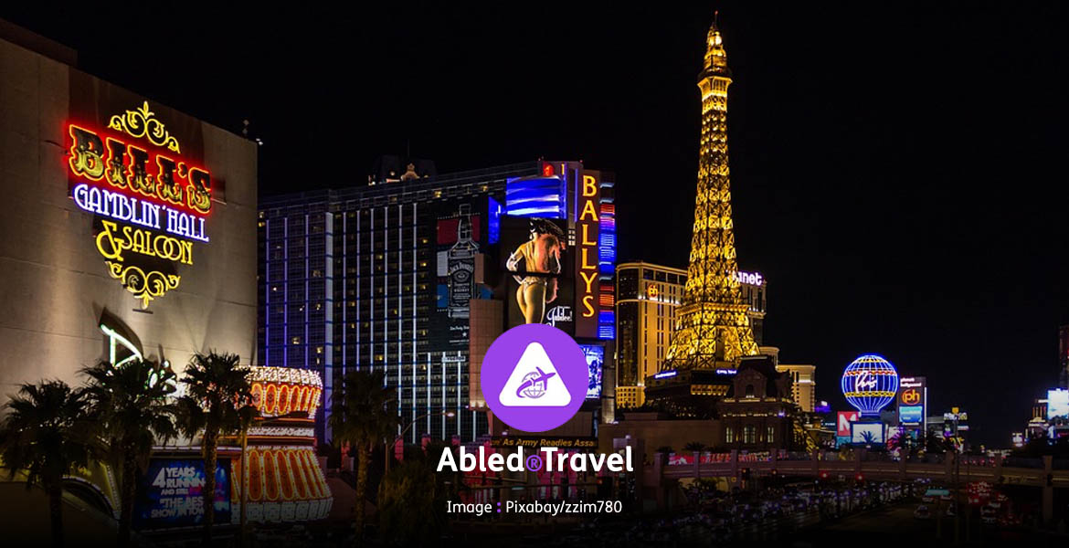 Abled.Travel: Photo of the Las Vegas strip lit-up at night from Bill's Gamblin' Hall & Saloon, past Bally's and further down the strip.