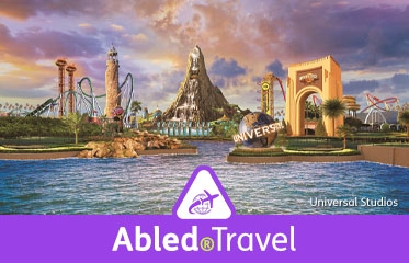 "Abled.Travel: Photo illustration of Universal Studios theme park in Orlando, Florida from a water view of the iconic arched entry gate to the volcano ""The Spirit of Krakatau""."
