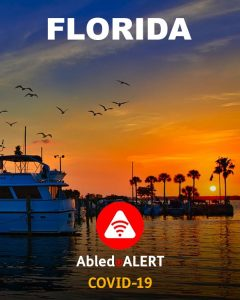 Florida - AbledALERT: COVID-19. Photo of a marina in Florida at sunset with a boat in the foreground and palm trees in the background.