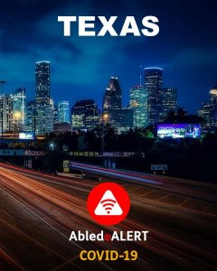 Texas - AbledALERT: COVID-19. Photo of the Houston skyline night with deep blue clouds behind illuminated buildings and streaks of light from vehicles on a freeway in the foreground.