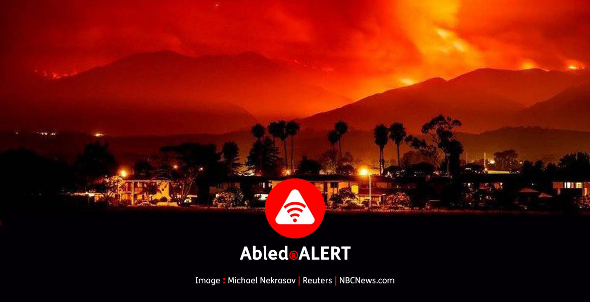 Abled.ALERT: EMERGENCY: California wildfires. Photo of residential area at night with mountains in the background lit up by wildfires turning the smoke in the sky red and orange.