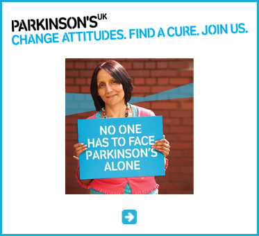 Abled Public Service Ad link to Parkinson's UK shows a headline that says Change attitudes, find a cure, join us, above a photo of a middle aged woman with dark reddish-brown hair holding a peacock blue sign with text that reads: 'No one has to face Parkinson's alone'.