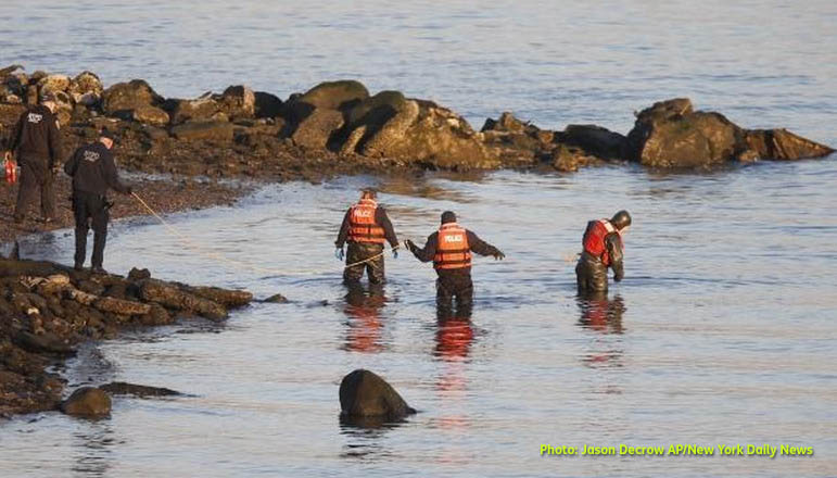 Photo shows a New York Police Department dive unit searching Friday along a rocky shoreline in Powell Cove in the Queens borough of New York. Photo by Jason Decrow of the Associated Press via the New York Daily News. Click here to go to their coverage of the story.
