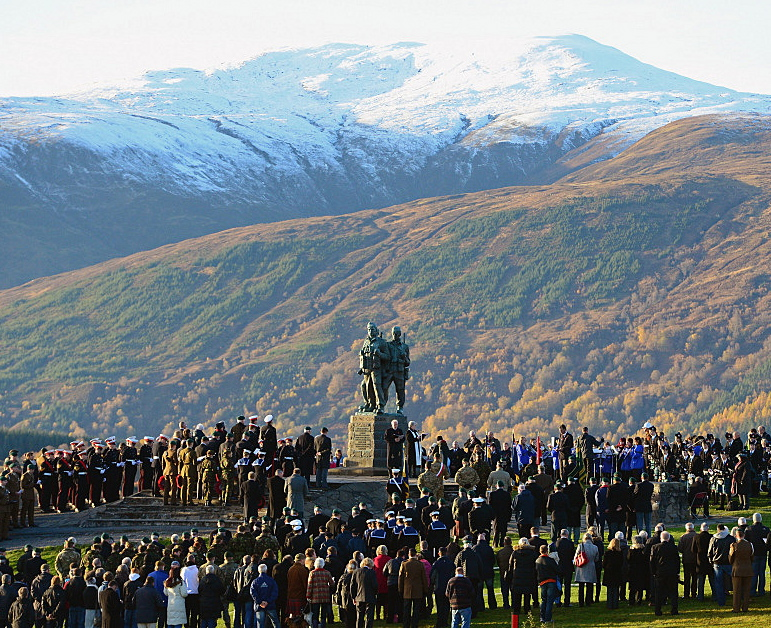 AbledWarriors-A photo shows Spean Bridge, United Kingdom — Commandos gather to commemorate and pay respect to the sacrifice of service men and women who fought in the two World Wars and subsequent conflicts on November 10, 2013 in Spean Bridge, Scotland. A cenotaph which features the statues of three commandos on top set against the rolling hills of Scotland with a snow-capped mountain in the background. (Jeff J. Mitchell/Getty Images)