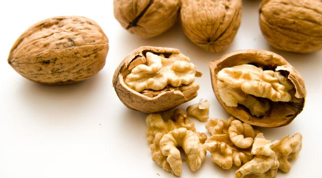 Photo shows whole and half-shelled walnuts on a white counter top.