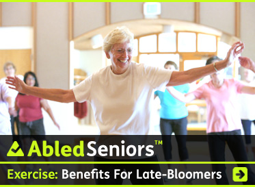 AbledSeniors Post Link Banner shows an older woman with white hair with glasses wearing a white t-shirt smiling as she stretches her arms out to her side as part of an exercise class while you see her classmates in the background with bright light from outside streaming in behind them through arched pane windows above the door to the gym. The headline reads: Exercise: Benefits for Late Bloomers. Click here to go to the post.