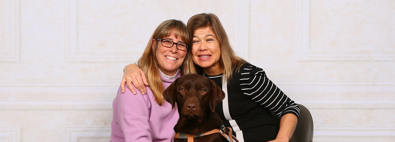 Photo shows Abled.com Co-Founder Laura Meddens on the right hugging her Seeing Eye trainer Janice Abbott with Laura's new Seeing Eye dog Nugget, a chocolate labrador,  sitting in front of them.
