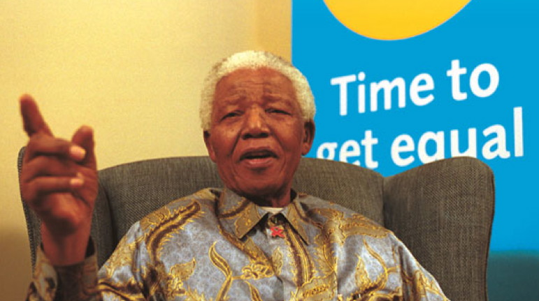 Former South African President Nelson Mandela is shown sitting in a wingback chair in a silver-grey shirt with gold and brown vines and leaves with an AIDS awareness ribbon pin clipped to his collar. He is emphasizing a point with his right hand and index finger while sitting in front of a poster for the Time To Get Equal Campaign.
