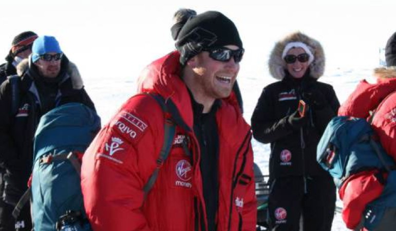 Photo shows Prince Harry wearing a red parka with a black sweater and toque with sunglasses having a laugh with other members of the Walking with the Wounded on a sunny day in Antarctica.