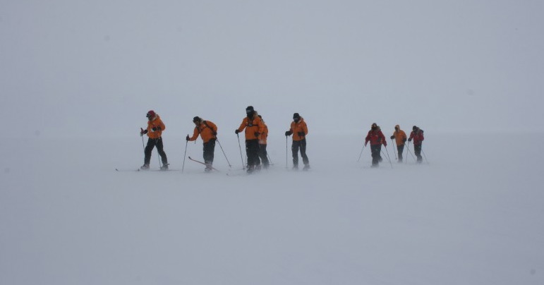 Photo shows members of the Walking WIth The Wounded at the South Pole trekking in harsh conditions with the wind whipping up the snow around them.