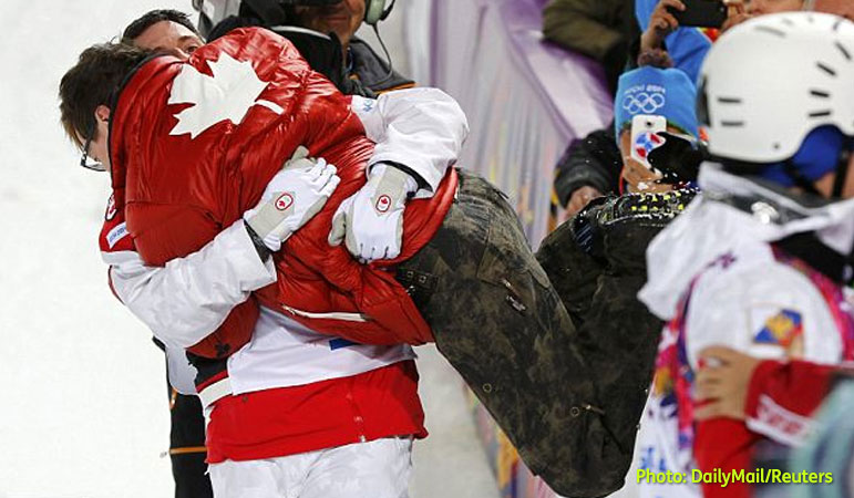 AbledPeople photo shows Canadian Olympic gold medalist Alex Bilodeau lifting his brother Frederic over the crowd barrier in a victory embrace.