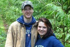 Photo of Alan Bejvi and Delaney Webb standing on a forest trail together. He is very tall wearing a camouflage cap with a blue hoodie under a beige jacket while she is wearing a matching hoodie and has mahogany brown hair. They are both smiling.