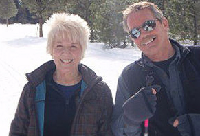 Photo of Larry and Sandy Miller. She has lightish blonde/white hair while he has sandy brown salt & pepper hair with a moustache and sunglasses. Both are dressed in light winter jackets and both are smiling at the camera.